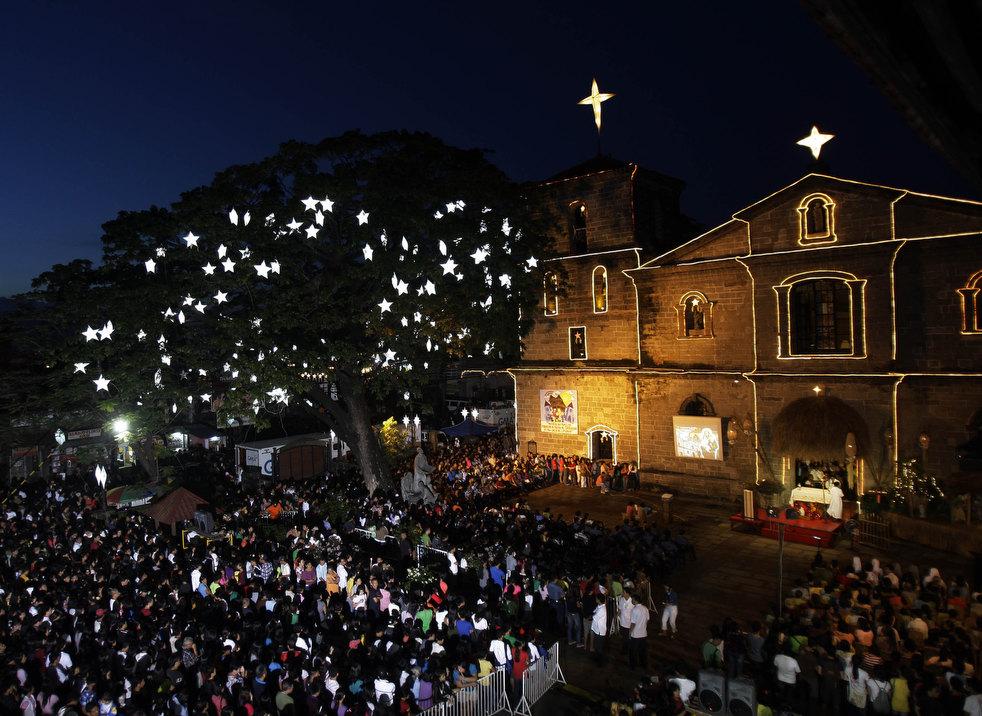 19. Освещенная огнями церковь во время утренней службы, символизирующей начало рождественской пятниц