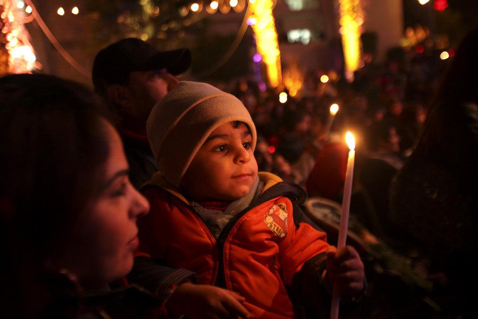 21. Палестинский мальчик с мамой на церемонии зажжения рождественской елки в Рамалле. (ZUMA24.com /