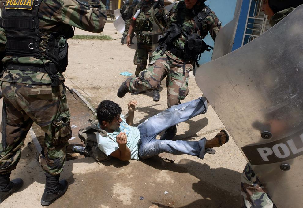 3. Перуанские полицейские избивают незаконного добытчика золота во время беспорядков в городе Пуэрто