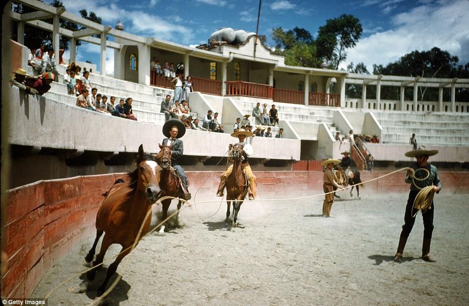 Местные жители наблюдают, как лихой наездник справляется с лошадью, 1952 год.
