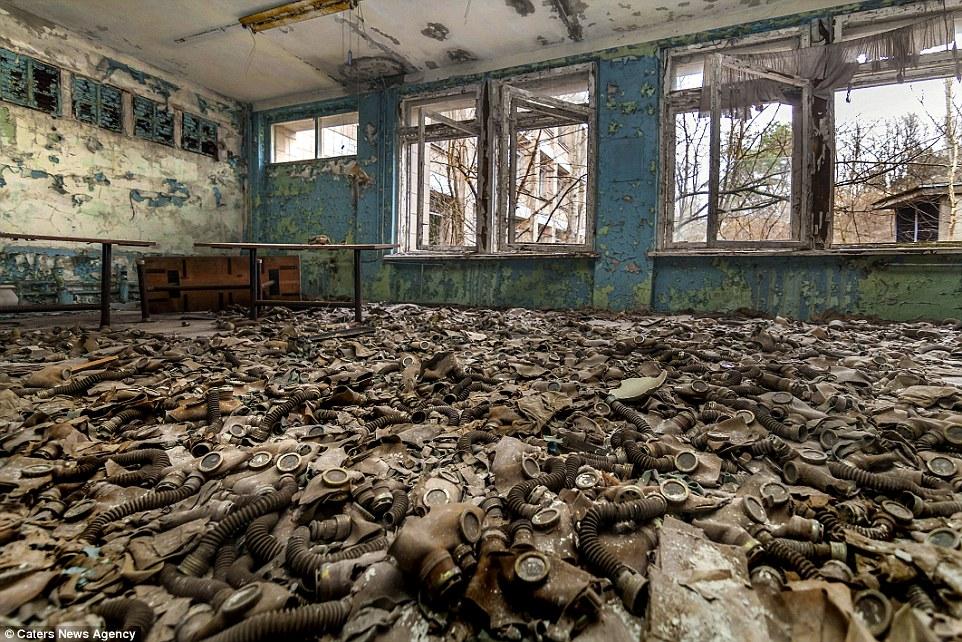 Целое море противогазов, оставленных в заброшенном здании, стены и крыша которого гниют и осыпаются.