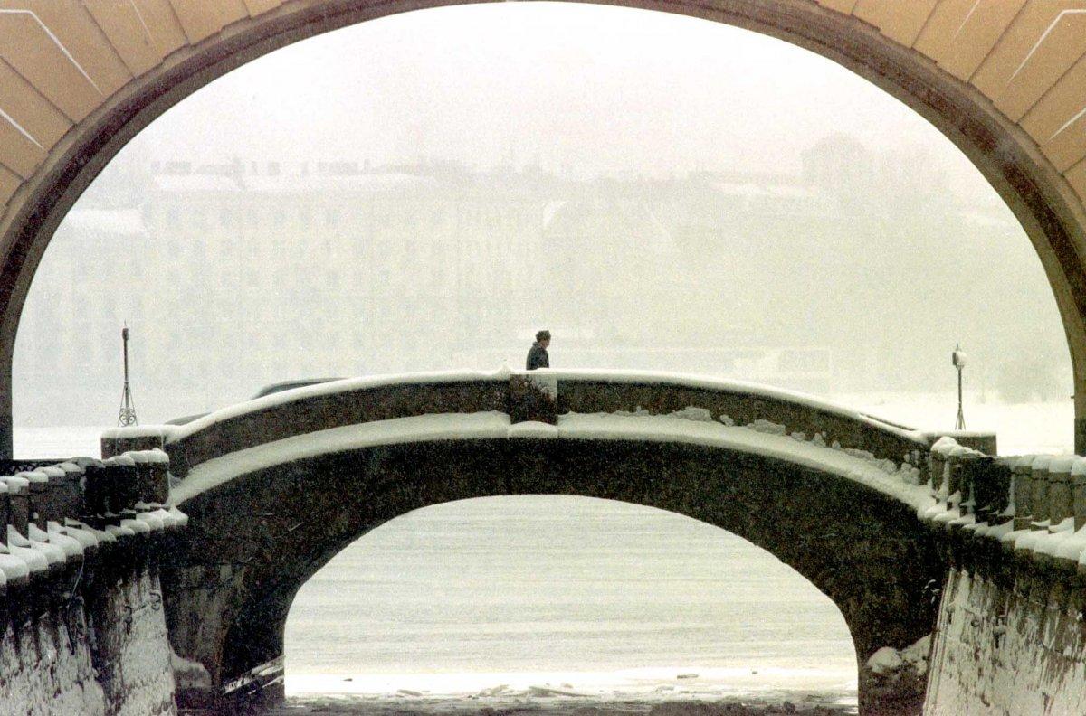 Мужчина идет по мосту в центре Санкт-Петербурга, апрель 1998 года.