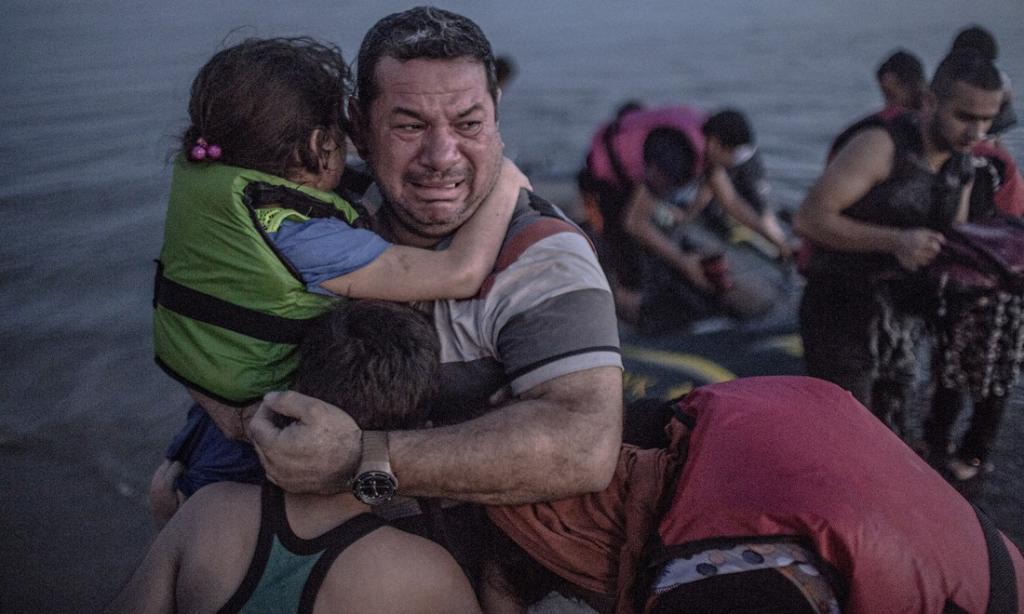 Сириец Лаит Маджид, обнимающий свою дочь и сына, мог погибнуть, добираясь из Турции на греческий ост