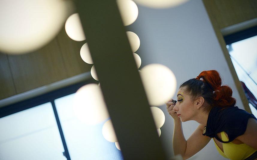 12. Танцовщица накладывает макияж.
