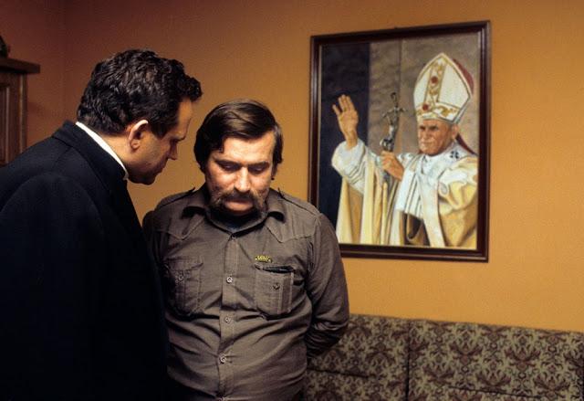 Лидер «Солидарности» Лех Валенса (справа), священник Генрих Янковский и портрет Иоанна Павла II, Вар