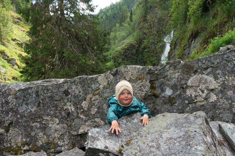 годовалый ребенок ползает на камнях и водопад