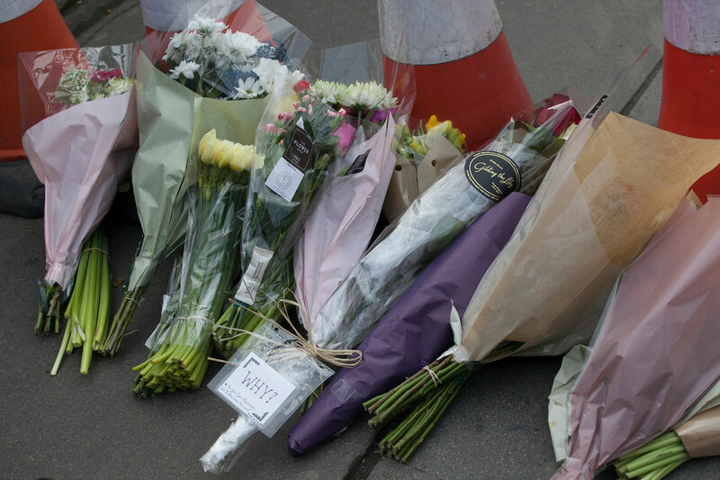 Flower tributes are left on the pavement on the edge of a police cordon near to parliament in London, Thursday,