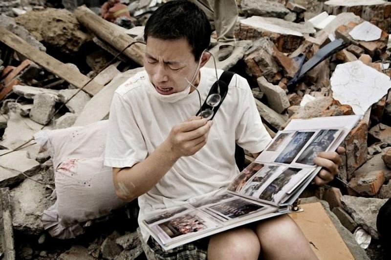19. Молодой человек смотрит семейный альбом, который нашел в щебне своего старого дома после землетр