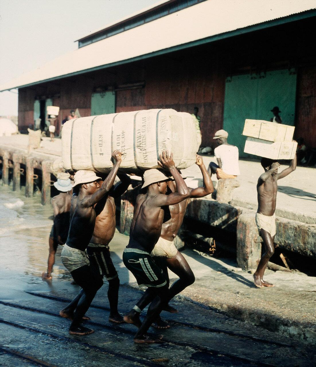 Носильщики переносят тюки с товарами из прибойных шлюпок на склад