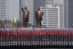 Студенты университета несут национальный флаг и две бронзовые статуи Ким Ир Сена и Ким Чен Ира во время военного парада в Пхеньяне, Северная Корея, 15.04.17 Вонг Майе-E, AP.png