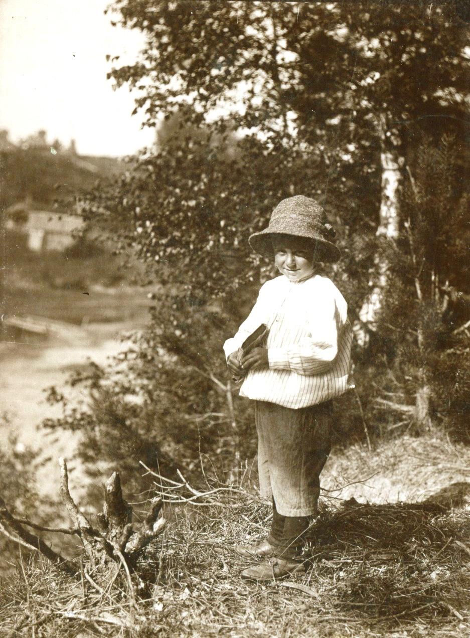 Шура Зворыкин на фоне берёзы на берегу водоёма. Муром, 1913