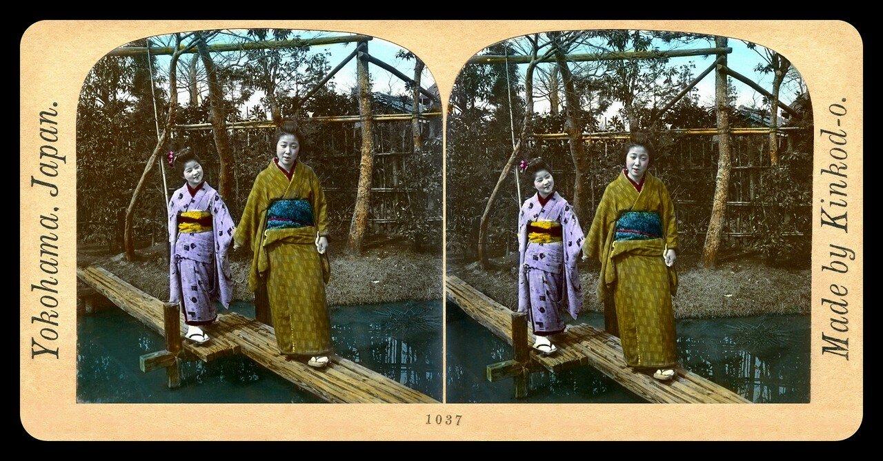 Иокогама. Старшая сестра ведет младшую по пешеходному мосту в местном парке