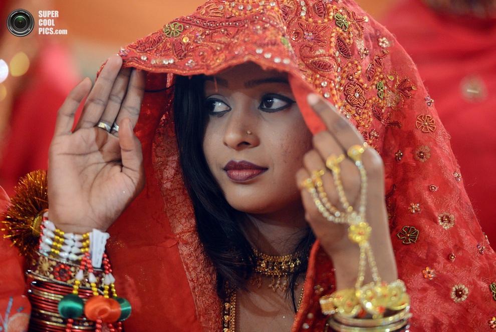 Одна из невест с любопытством рассматривает «подруг» по свадьбе, Карачи, Пакистан. (ASIF HASSAN/