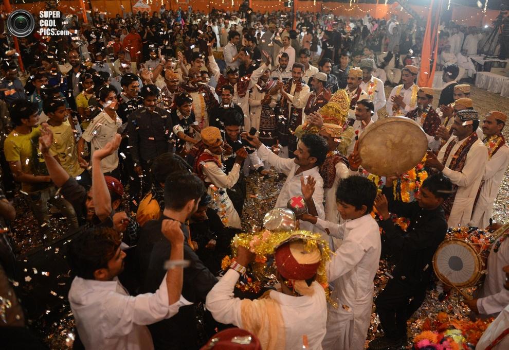 Танцующие женихи и члены их семей — здесь царит атмосфера праздника. (ASIF HASSAN/AFP/Getty Imag