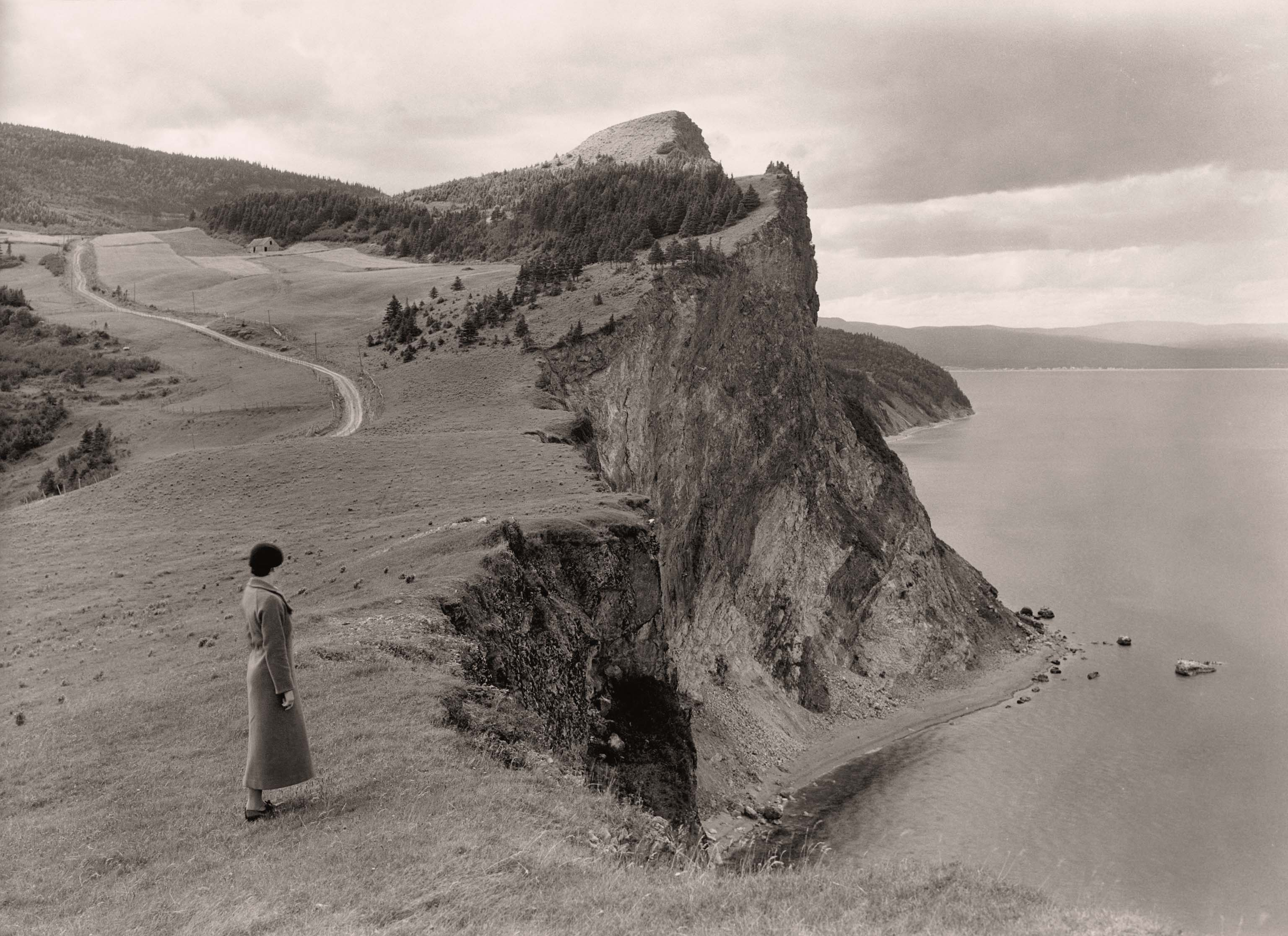 A woman stands before limestone cliffs in the Gaspe Peninsula, Quebec, September 1934..jpg
