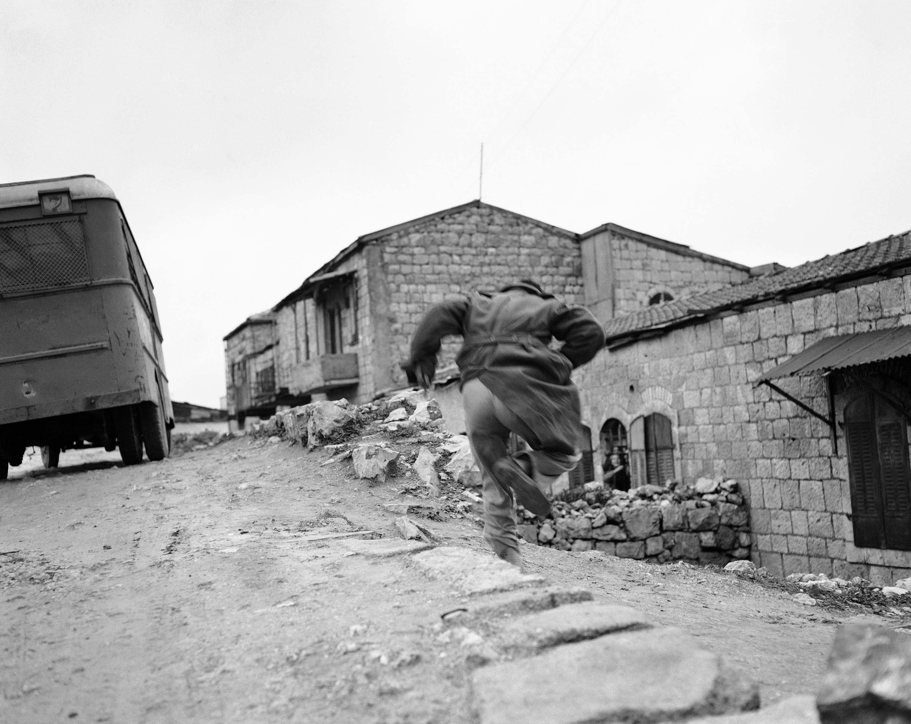 Застигнутый под открытым небом еврей пытается убежать, когда по нему стреляет арабский снайпер.в Монтефиоре, еврейском квартале  Иерусалима.  Январь