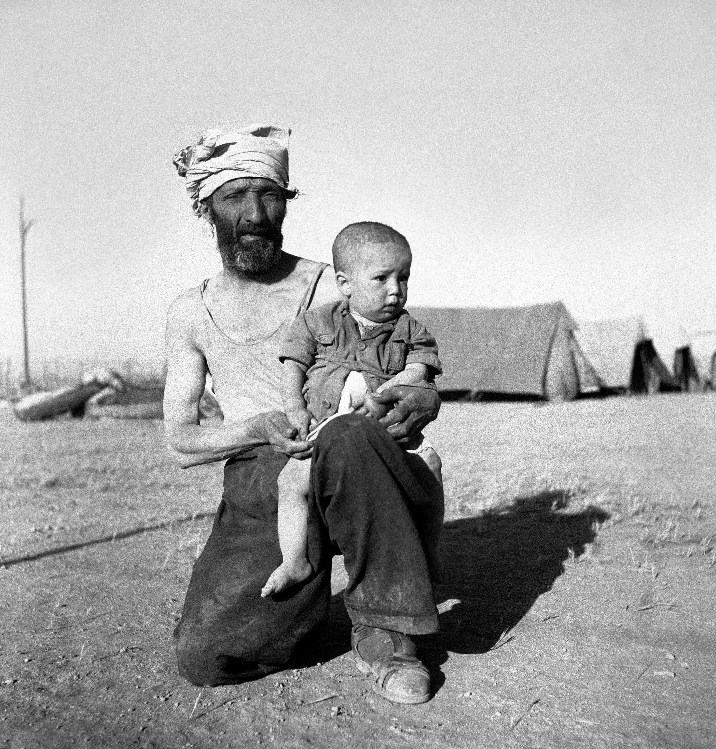 Годовалый Израиль Коперлов на колене у своего отца, Хаима Коперлова, ожидающего проверки охранниками Легиона в Трансиорданском лагере. 4 июня