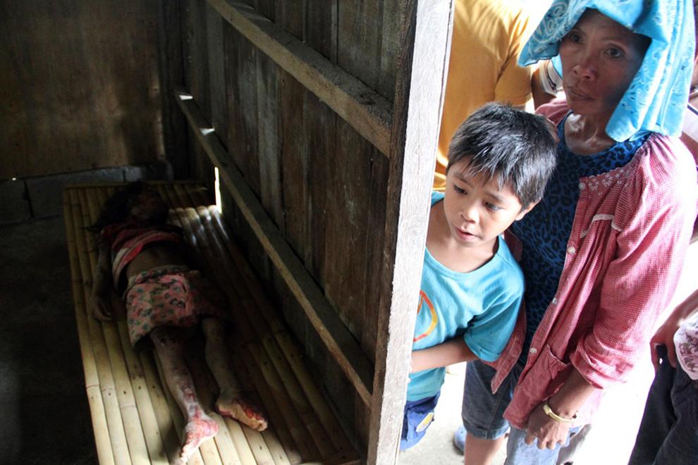 8. Местные жители смотрят на тело девочки, погибшей при оползне в отдаленном маленьком поселении зол