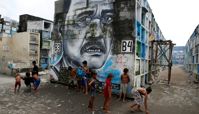 Children play in front of a mural at Navotas Public Cemetery, Metro Manila in the Philippines, Octob