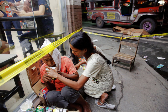 A street vendor is comforted at the scene where a man was killed shortly before midnight by unknown