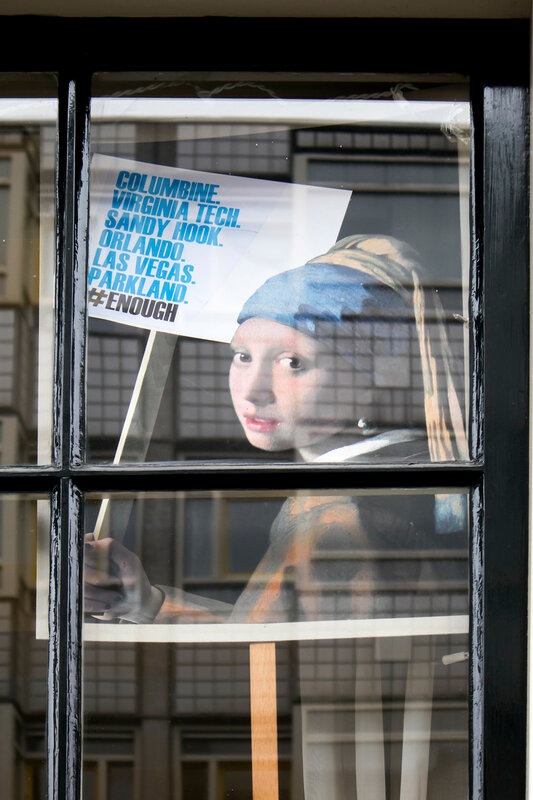 the placard of Vermeer The girl with a pearl earring with protest agains shooting in USA
