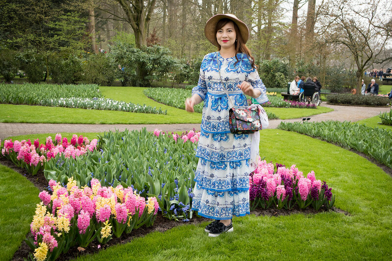 Woman in traditional holland dress poses in the botanical garden of Keukenhof in spring