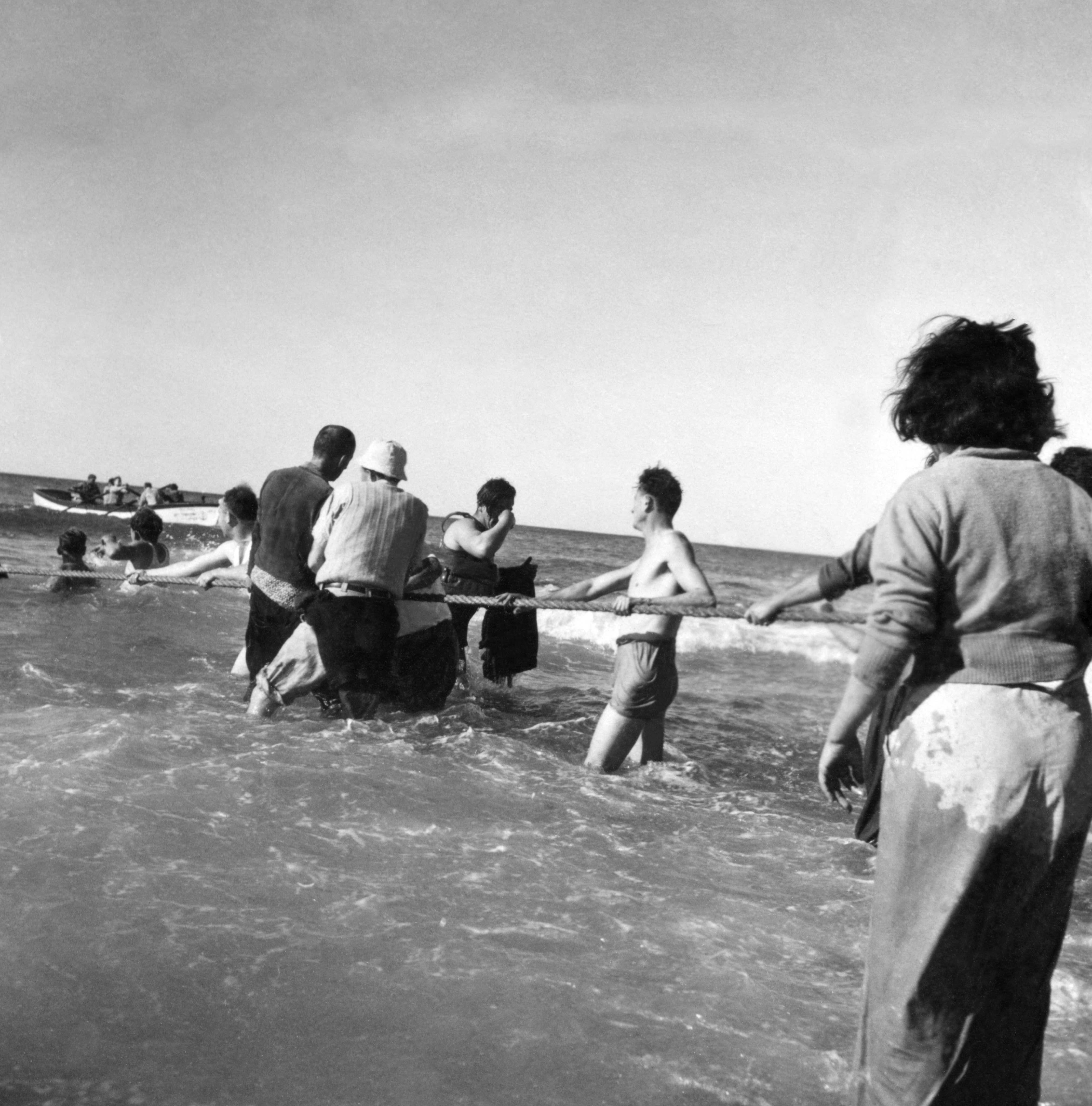 Люди тянут канат, связывающий  судно с берегом во время прибытия новой партии нелегальных эмигрантов в Нагарию. 13 января