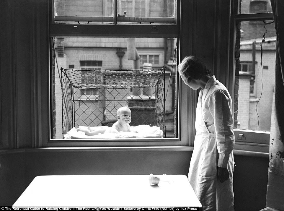 Младенец дышит свежим воздухом в клетке, вывешенной за окно.