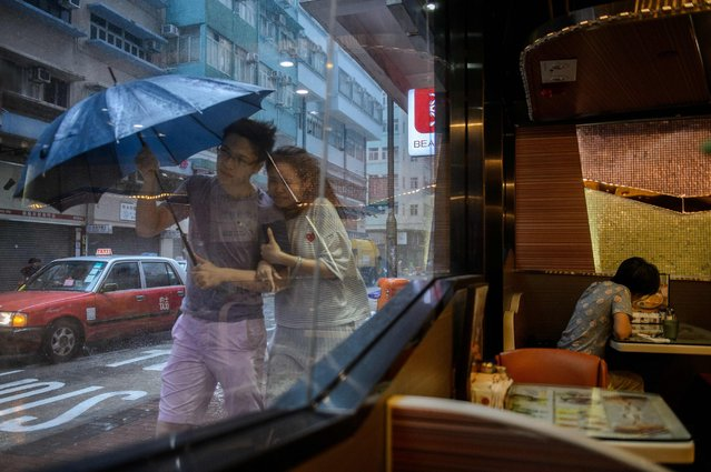 A couple walks in the heavy rain as Typhoon Haima makes landfall in Hong Kong, October 21, 2016. (Ph