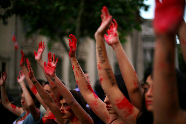 Demonstrators rise their painted hands during a peaceful march against gender violence in Santiago,