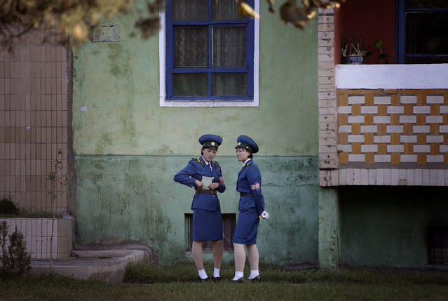 North Korean traffic police women chat next to a residential building while off duty Tuesday, Octobe