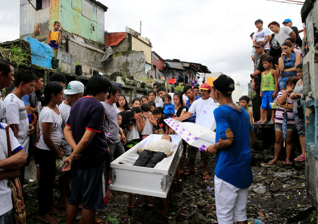 Relatives and friends gather in front of the coffin to view the body of Apolinario Eyana Jr., who wa