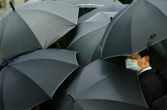 A mourner wearing a mask to ward off SARS hides under an umbrella during the funeral of SARS doctor