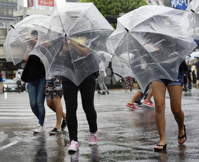 Pedestrians walk under heavy rain and wind in Tokyo, Japan, in this photo taken by Kyodo August 22,