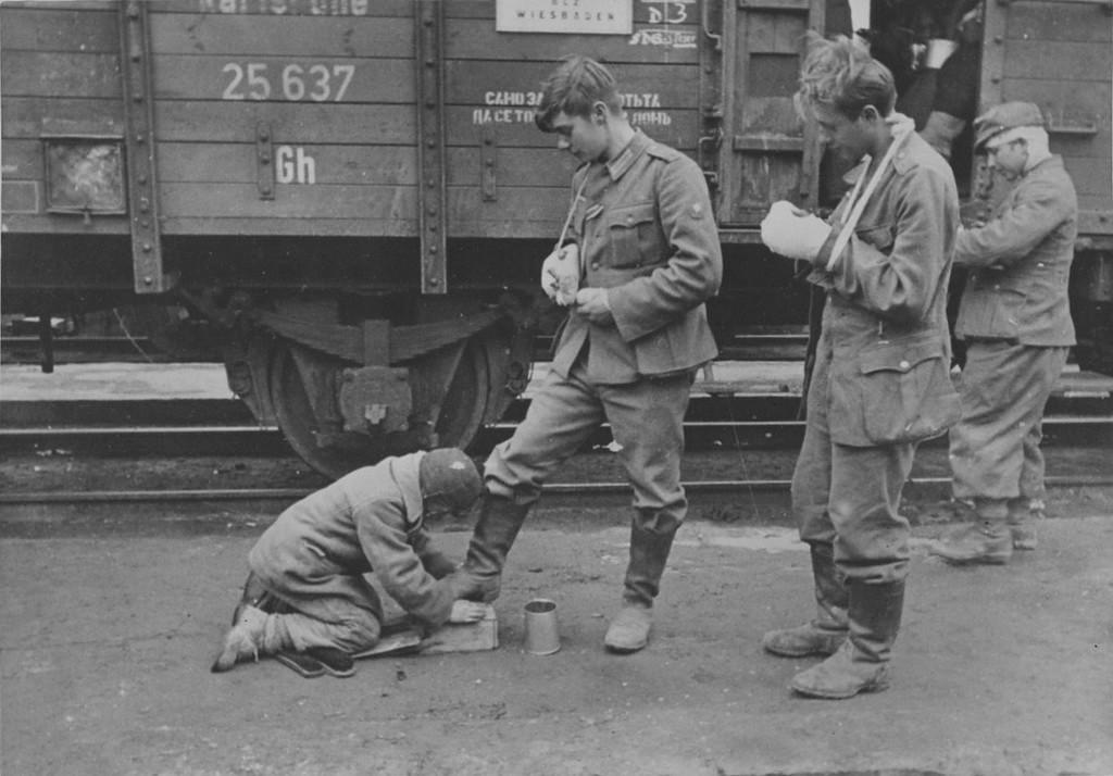 Мальчик чистит сапоги раненным немецким солдатам. 1943 год.