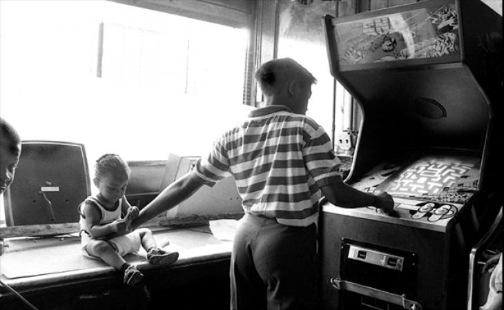 14-летняя Элла играет в Pacman, рядом ее малыш. Бруклин, 1983.