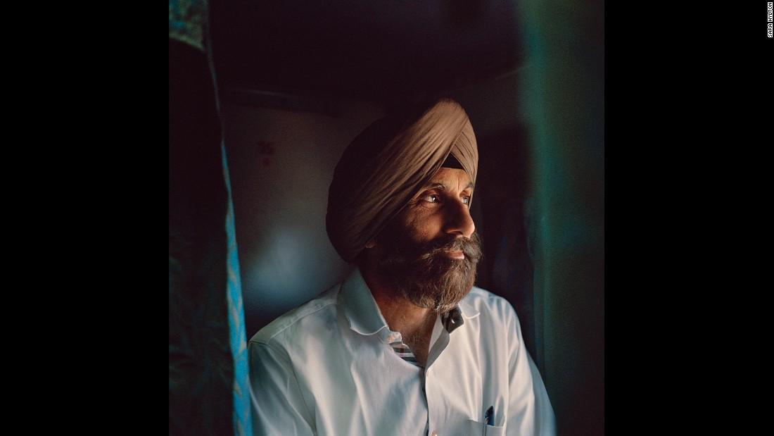 Мужчина смотрит из окна своего поезда. В отличие от множества других индийцев, у его семьи есть возм