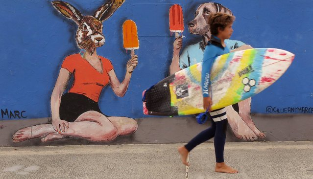 A young surfer walks past street art on the way to surf at Sydney's iconic Bondi Beach on Octob