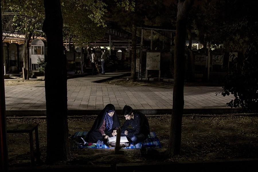 19. Парочка читает Коран на религиозной церемонии в память о смерти Имама Али на кладбище в пригород