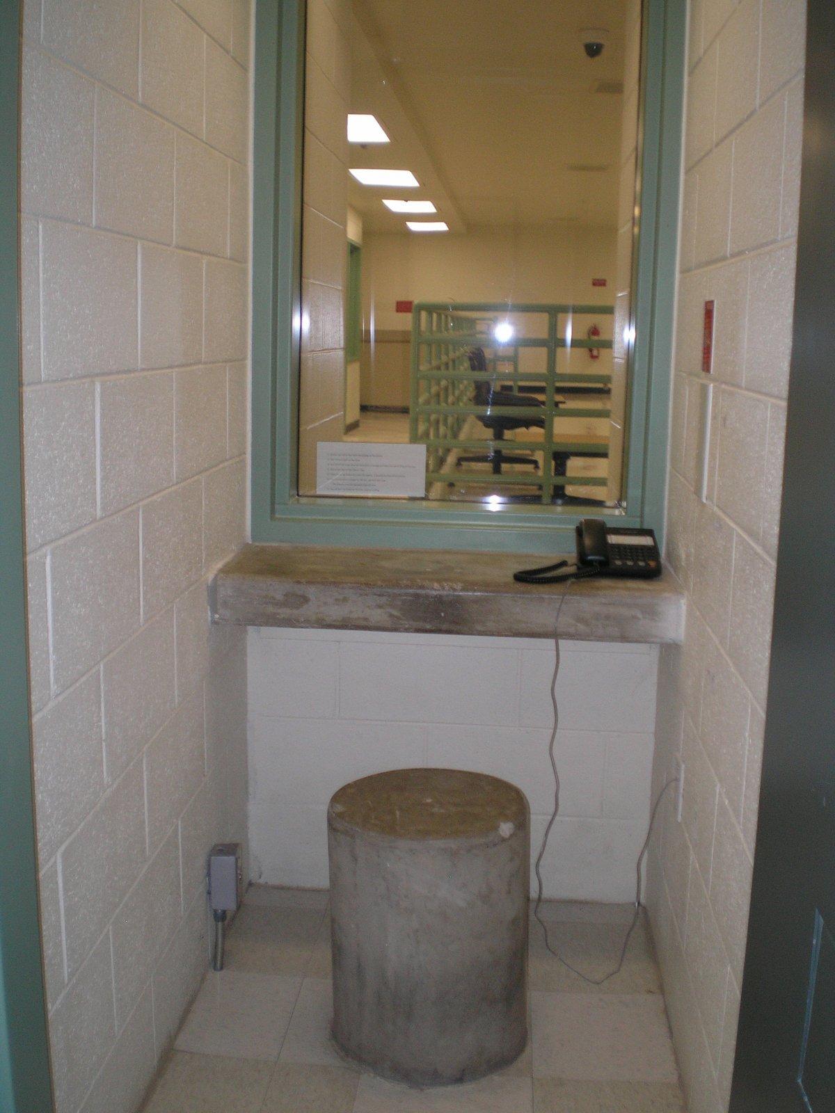 Во время посещений заключенные используют телефон для общения через стеклянную панель. На это время