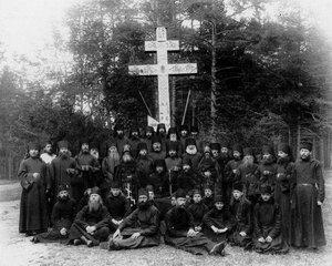 Группа монахов и схимников с настоятелем монастыря около надгробного креста.