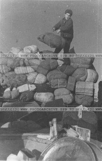 Разгрузка багажа эвакуируемых с вагонеток на причал порта Кобона. 1942 г.