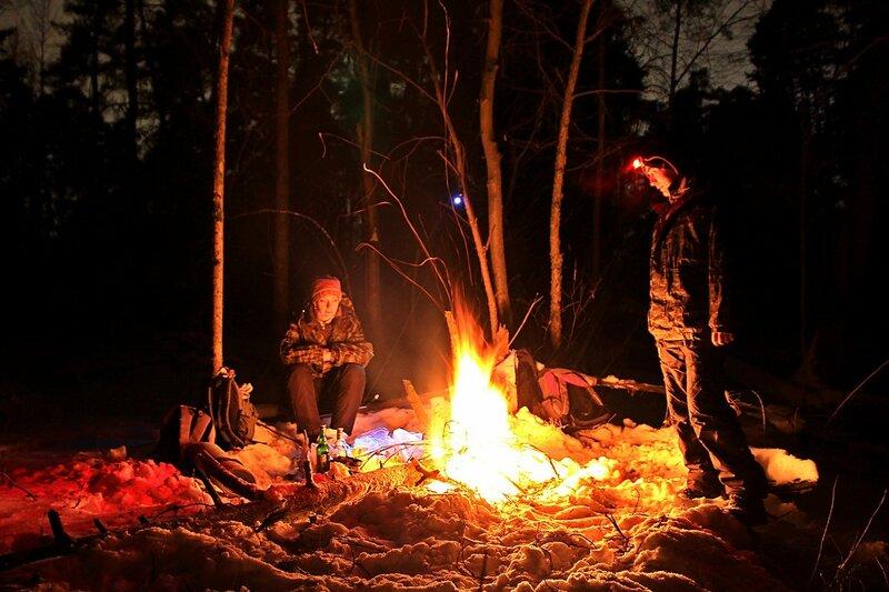 Костёр в ночном зимнем лесу: треки вылетающих искр и свет фонаря