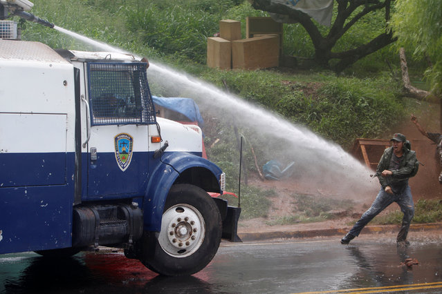 A demonstrator evades a police water canon during a protest to demand justice over the murder of env