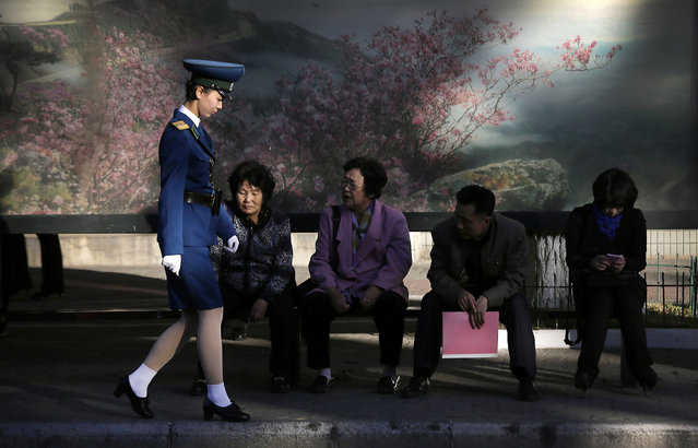 A North Korean traffic police woman walks past commuters waiting at a bus stop at the end of a workd