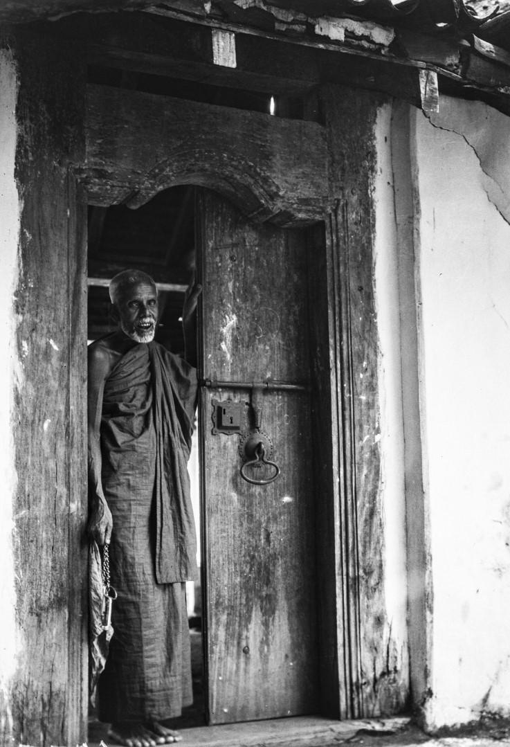 425. Буддийский монах стоит в дверях с ключом в руке