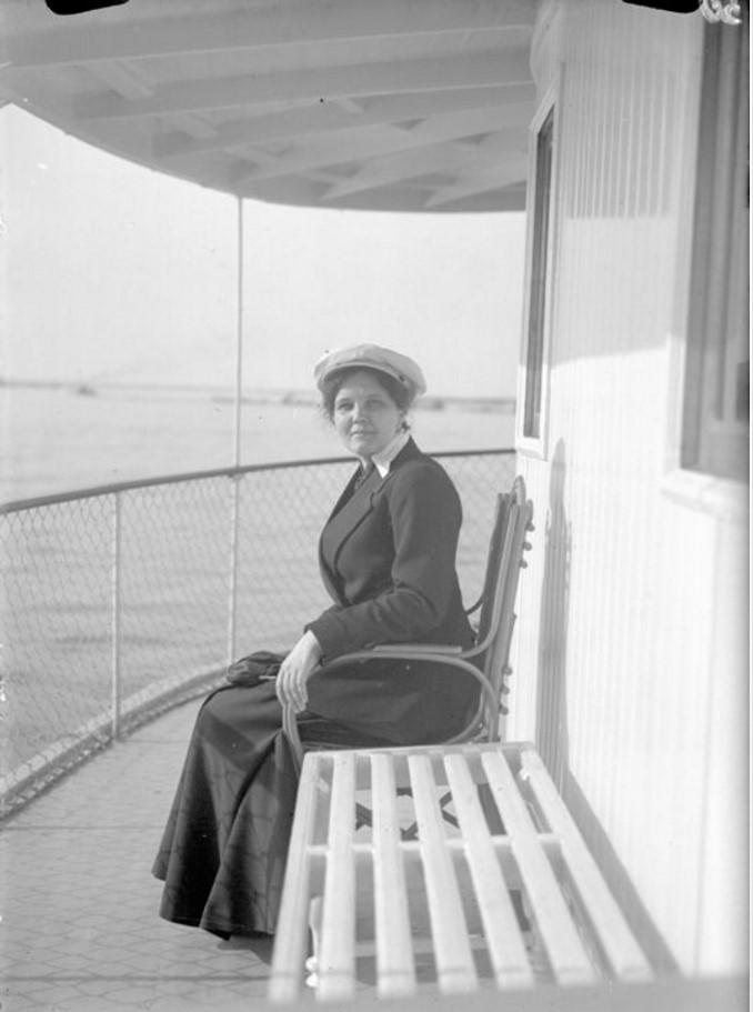 1915. Дама в темном платье на палубе парохода (сидит на стуле)