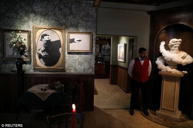 Официант отеля на фоне работ Бэнкси. В здании расположена художественная галерея с работами на полит