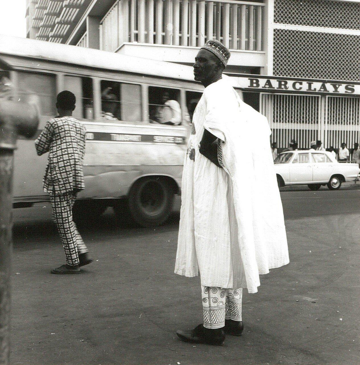 Уличная сцена в современном центре города с нигерийцем в праздничной одежде