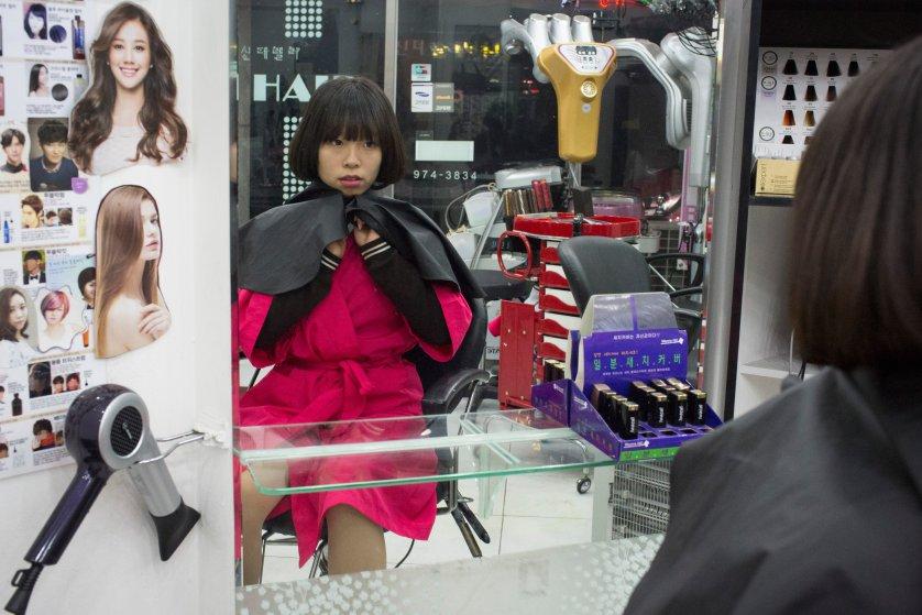 Кьёнг-ок смотрит на себя в зеркало — ее тетя постригла и уложила ей волосы в своем салоне красоты в